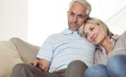 Relaxed couple sitting on sofa Stock Photos