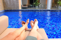 Relaxed couple sitting on sofa with swimming pool view Stock Photo
