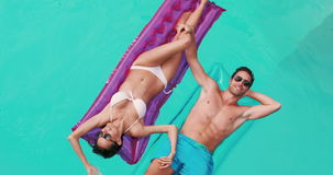 Relaxed couple with sunglasses on lilo. In the pool stock footage