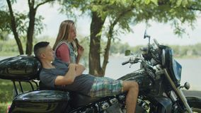 Relaxed couple talk on motorcycle during roadtrip stock video