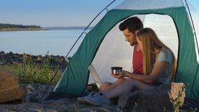 Relaxed couple of travelers camping at seaside stock footage