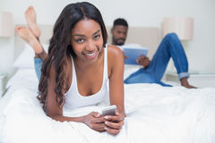 Relaxed couple using technology on bed Royalty Free Stock Photos