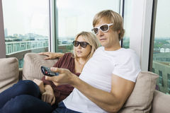 Relaxed couple wearing 3D glasses and watching TV at home Royalty Free Stock Photo