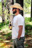Relaxed Cowboy. A relaxing day off for an unshaven cowboy standing wearing a white straw western hat holding a drink. Trees in background. Shallow depth of field Royalty Free Stock Photography
