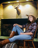Relaxed Cowgirl. A pretty teen cowgirl relaxed indoors by a fireplace royalty free stock photography