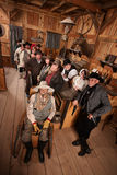 Relaxed Crowd with Guns in Saloon. Relaxed customers in old west tavern with weapons at their sides Stock Photos