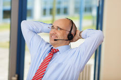 Relaxed Customer Service Executive With Hands Behind Head. Relaxed male customer service executive with hands behind head looking away in office Royalty Free Stock Image