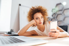 Relaxed cute curly young woman using mobile phone in office Royalty Free Stock Photo
