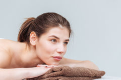 Relaxed cute young woman lying on towel in spa salon Royalty Free Stock Photography