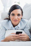 Relaxed dark hair woman lying on the couch sending messages Stock Photography