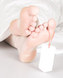 Relaxed dead body with toe tag Royalty Free Stock Photography