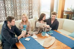 Relaxed diverse friends in bathrobes sitting at lounge zone of bathhouse. Cheerful young male and female friends in soft bathrobes sitting at the table with cups stock images