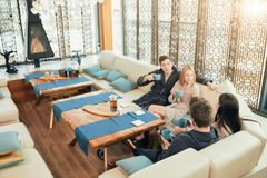 Relaxed diverse friends in bathrobes sitting at lounge zone of bathhouse. Cheerful young male and female friends in soft bathrobes sitting at the table with cups royalty free stock images