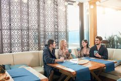 Relaxed diverse friends in bathrobes sitting at lounge zone of bathhouse. Cheerful young male and female friends in soft bathrobes sitting at the table with cups royalty free stock image
