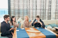 Relaxed diverse friends in bathrobes sitting at lounge zone of bathhouse. Cheerful young male and female friends in soft bathrobes sitting at the table with cups stock image