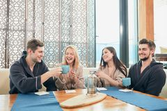 Relaxed diverse friends in bathrobes sitting at lounge zone of bathhouse. Relaxed diverse friends in bathrobes relaxing at lounge zone of bathhouse, drinking hot stock photography