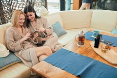 Relaxed diverse friends in bathrobes sitting at lounge zone of bathhouse. Two young caucasian women dressed in bathrobes sitting at table in the cozy lounge of a royalty free stock photo