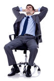 Relaxed and dreaming business man. Sits on office chair over white background Royalty Free Stock Photography