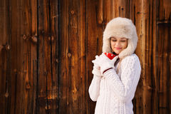 Relaxed and dreamy woman with red cup near rustic wood wall Stock Images