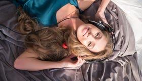 Relaxed e feliz Música de escuta da jovem mulher atrativa ao encontrar-se na cama em casa Imagens de Stock