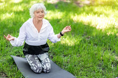 Relaxed elderly lady recreating in park doing yoga asana Royalty Free Stock Images