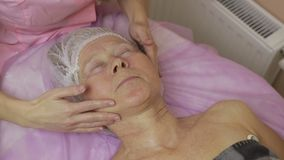 Relaxed elderly woman getting spa face treatment. Relaxed elderly woman with eyes closed getting spa face treatment in beauty salon. Female hands of professional stock video footage