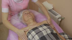 Relaxed elderly woman getting spa massage. Relaxed elderly woman with closed eyes receiving spa massage in beauty salon. Beautician hands working on massaging stock footage