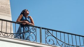 Relaxed elegance tanned female in dress enjoying sunshine standing on balcony