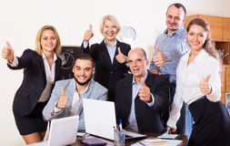 Relaxed employees sitting at desk Stock Image