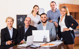 Relaxed employees sitting at desk Stock Photos