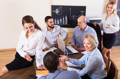 Relaxed employees sitting at desk Royalty Free Stock Photo