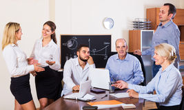 Relaxed employees sitting at desk Royalty Free Stock Images