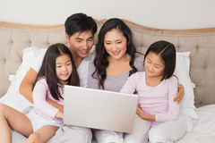 Relaxed family of four using laptop in bed. Happy relaxed family of four using laptop in bed at home Royalty Free Stock Photography