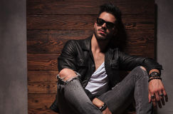 Relaxed fashion man in sunglasses and leather jacket is sitting. On wood bakground in studio Royalty Free Stock Photos