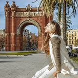 Relaxed fashion-monger near Arc de Triomf sitting on parapet. In Barcelona for a perfect winter. relaxed trendy fashion-monger in earmuffs near Arc de Triomf in Royalty Free Stock Photo