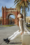 Relaxed fashion-monger near Arc de Triomf sitting on parapet Royalty Free Stock Image