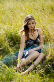 Relaxed Fashion Woman Sitting In Sunny Field Royalty Free Stock Images