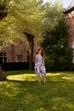 Relaxed woman standing grass tree, Groot Begijnhof, Leuven, Belgium stock images