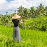 Relaxed fashionable caucasian female tourist wearing small backpack and traditional asian paddy hat looking at beautiful stock images