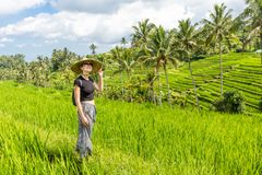 Relaxed fashionable caucasian female tourist wearing small backpack and traditional asian paddy hat walking among royalty free stock photo