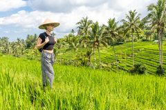 Relaxed fashionable caucasian female tourist wearing small backpack and traditional asian paddy hat walking among royalty free stock images