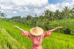 Relaxed fashionable caucasian woman wearing red asian style kimono and traditional asian paddy hat, arms rised to sky stock photography