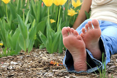 Relaxed feet. Resting in front of the flowers Stock Photos