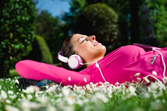 Relaxed female athlete resting and day dreaming. Relaxed female athlete resting and listening music with headphones after workout. Woman lying down and day stock image