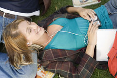 Relaxed Female College Student Enjoying Music Royalty Free Stock Photography