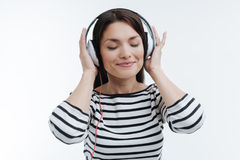 Relaxed female enjoying while listening music. Deep in thoughts. Amazing woman keeping smile on her face and putting both hand on headphones while standing over Royalty Free Stock Photography