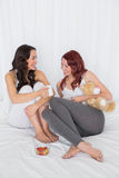 Relaxed female friends chatting over coffee in bed. Cheerful relaxed female friends chatting over coffee in bed at home Stock Image
