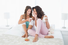 Relaxed female friends with coffee cups gossiping in bed Stock Photo