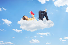 Relaxed female reading a novel and lying on clouds Royalty Free Stock Photos