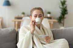 Relaxed female sit on couch enjoying cup of coffee. Happy female sit on couch in warm blanket enjoying cup of coffee, girl relax on cozy sofa drinking aromatic royalty free stock photography